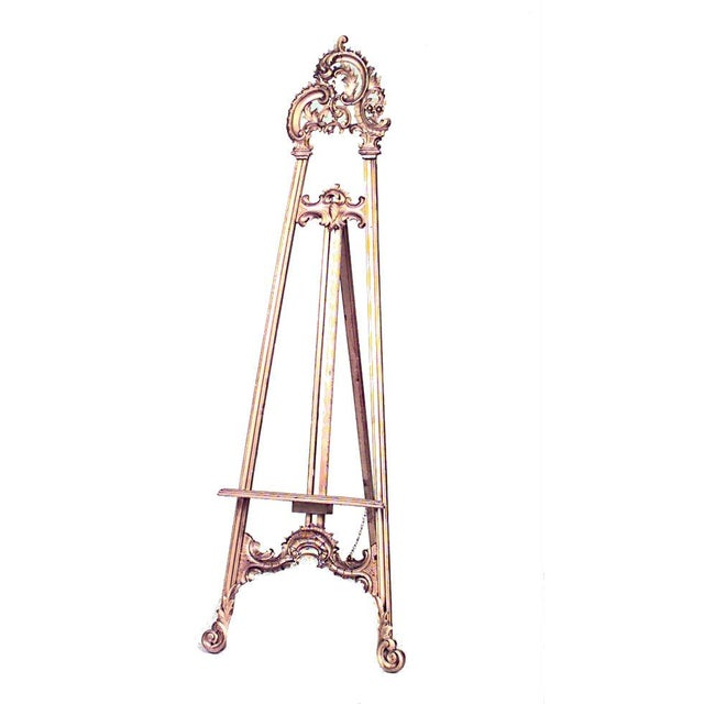 French Louis XV style (19/20th Cent) gilt easel stand with ornate carved triple scroll top.
