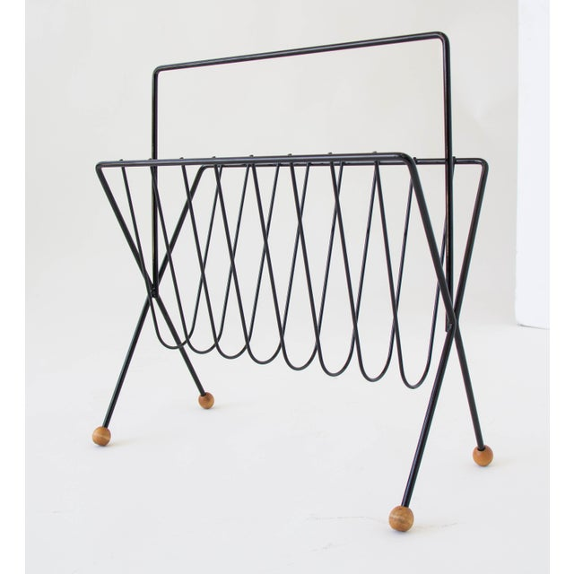 American made wire magazine rack by New York designer Tony Paul. The rack has a skeletal frame with bent spokes to hold...