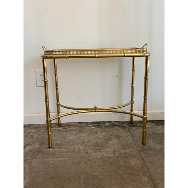 This sexy vintage brass side table features a glass top with unique mirror frame. Beautiful vintage brass patina. The tray...
