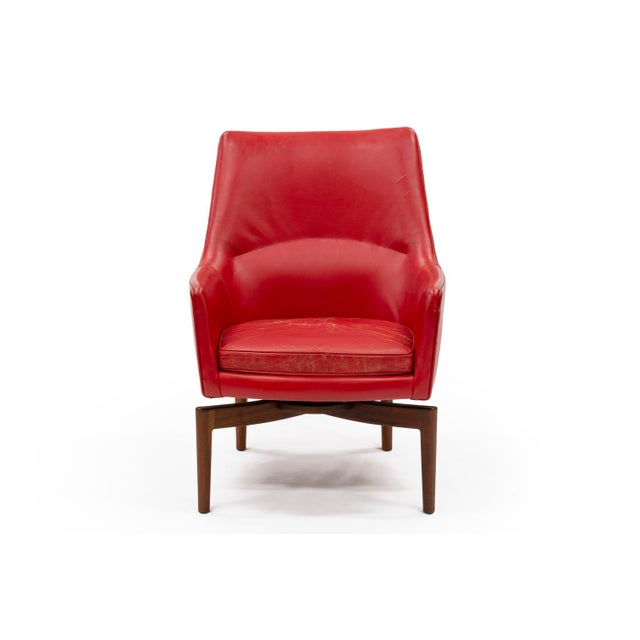A stunning swivel lounge chair wrapped in its original red leather designed by Jens Risom. This particular chair is a...