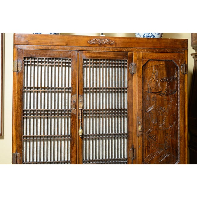 Lovely, elm and walnut Japanese clothes press with drawers, cabinets and shelves. Intricate carving on the one door and...