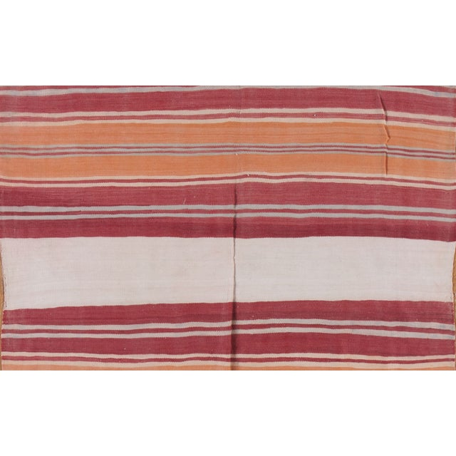 Bright orange, cranberry red, ivory and platinum grey run throughout this vintage Moroccan Kilim runner rug. The super...
