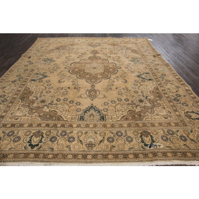 Vintage hand-knotted Tabriz rug with a medallion design, distressed areas consistent with age and history, minor old...
