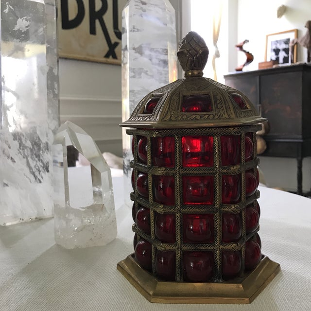 Vintage Beautiful caged glass lidded jar. Latticework brass surrounds deep red glass bubbling out from within.
