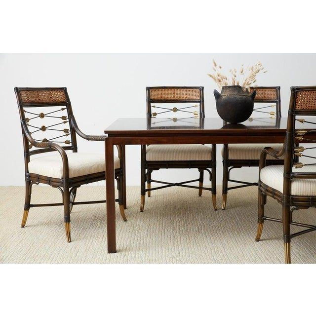 Amazing set of four bamboo rattan dining armchairs made in the style and manner of McGuire. The chairs feature...