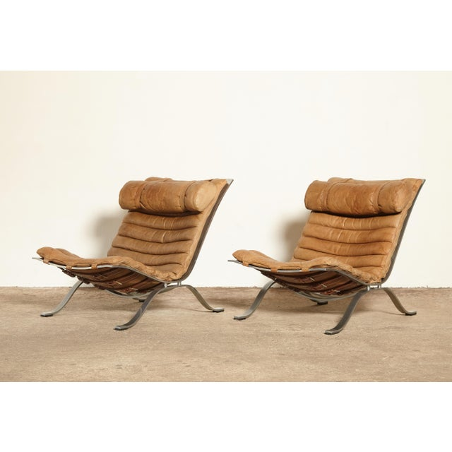 A stunning original pair of Arne Norell Ari Chairs, Norell Mobler, Sweden, 1970s. In rarely seen cognac / tan buffalo...