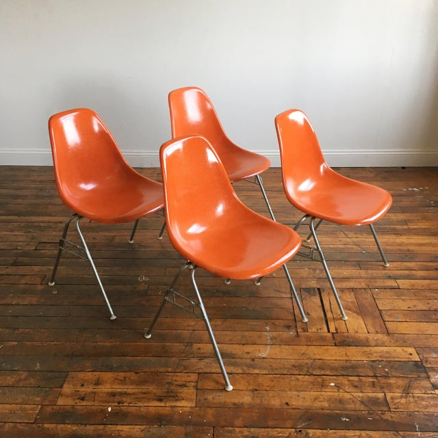 Set of 4 vintage Eames for Herman Miller molded fiberglass shell chairs on zinc stacking bases in Red Orange.