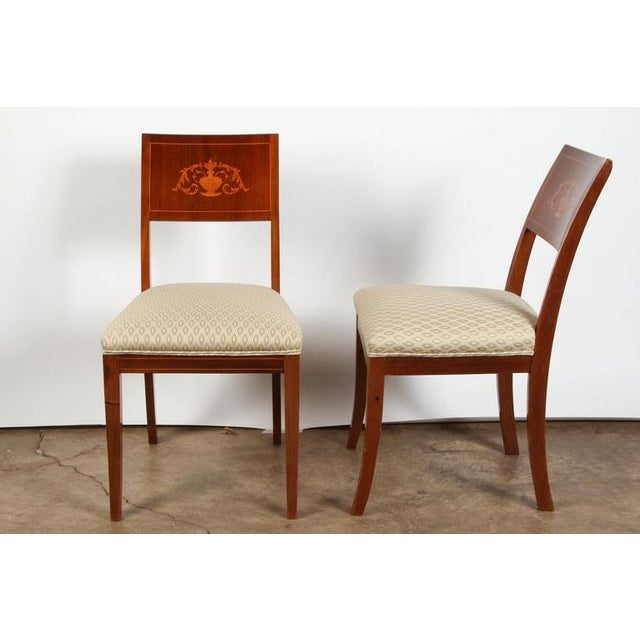 A pair of 19th Century Danish inlaid mahogany chairs circa 1820. They have been reupholstered with double welt in a...