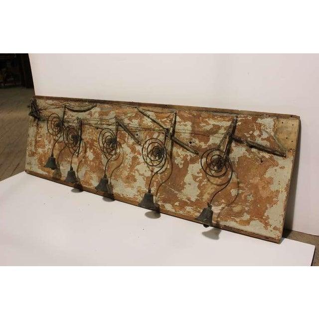 Antique Folk Art Byron mechanical bells on wooden board.