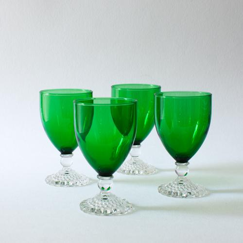 The cheerful pop of vibrant emerald green is balanced by the decorative, clear glass foot that features a bubble texture...