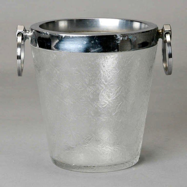Circa 1930s ice bucket of clear crystal with an overall design topped with a silver plated rim and round handles.