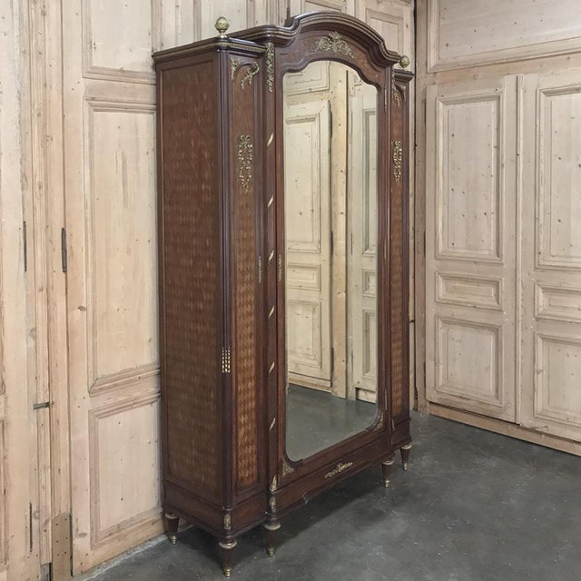 19th Century Louis XVI Bronze Mounted Mahogany Armoire by Schmit of Paris is an example of the Belle Epoque magnificence...