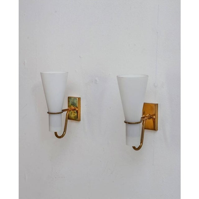 A pair of Asea brass and opaline glass bedside wall lamps. From the wall mount two arms extend that hold a trumpet shaped...