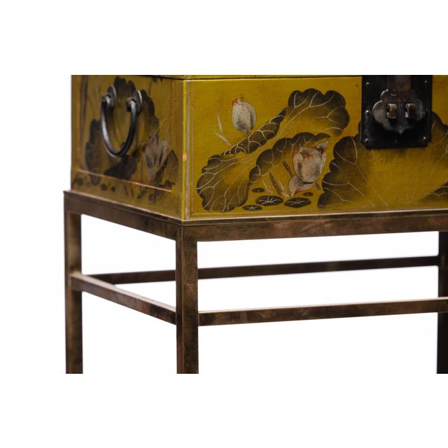 This lacquered chartreuse water buffalo hide leather box featuring a hand-painted lotus scene with touches of gold and...
