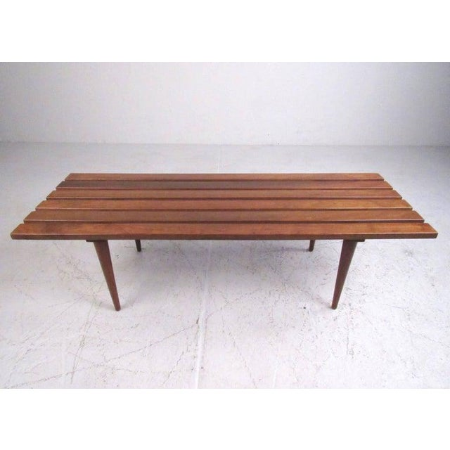 This vintage slat coffee table features Mid-Century construction with tapered legs, walnut finish, and sturdy...