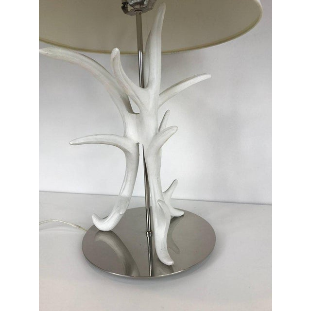 A pair of white painted faux antler table lamps mounted on circular chrome base. Shade for display purposes only.