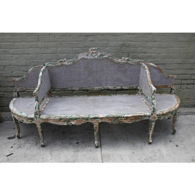 French, circa 1930s beautifully painted and caned three section sofa. The sofa stands on eight cabriole legs that end in...
