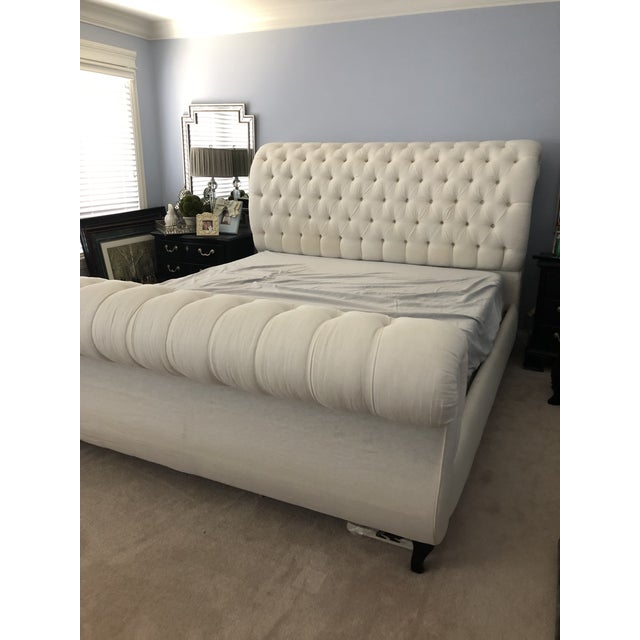 Classic tufted sleigh bed with off-white linen upholstery. Contemporarily made.