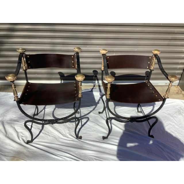 Stylish pair of Italian iron, brass and leather savaronola style chairs. The chairs have new, rich brown leather, with...