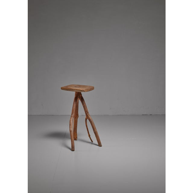 A wooden craft stool by Brazilian artist Fernando da Ilha do Ferro. The stool has a rectangular (28 by 24 cm) seating and...