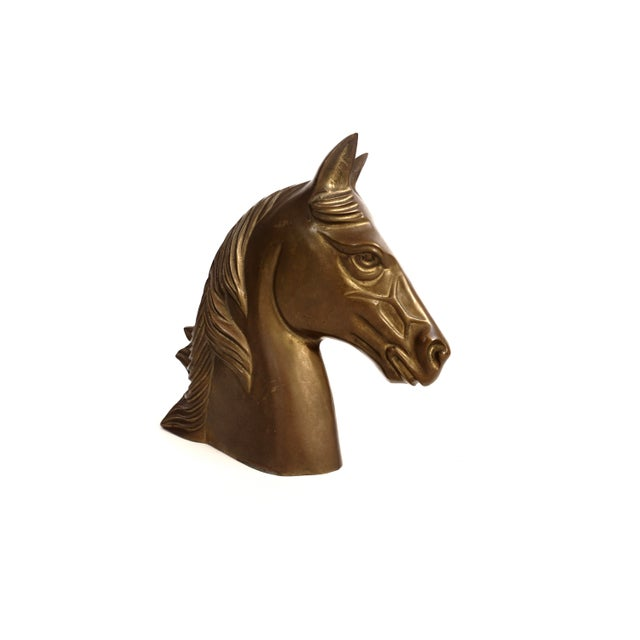 Showcasing immense detail and elegance, this pleasantly imposing vintage horse head statue is made of solid brass with...