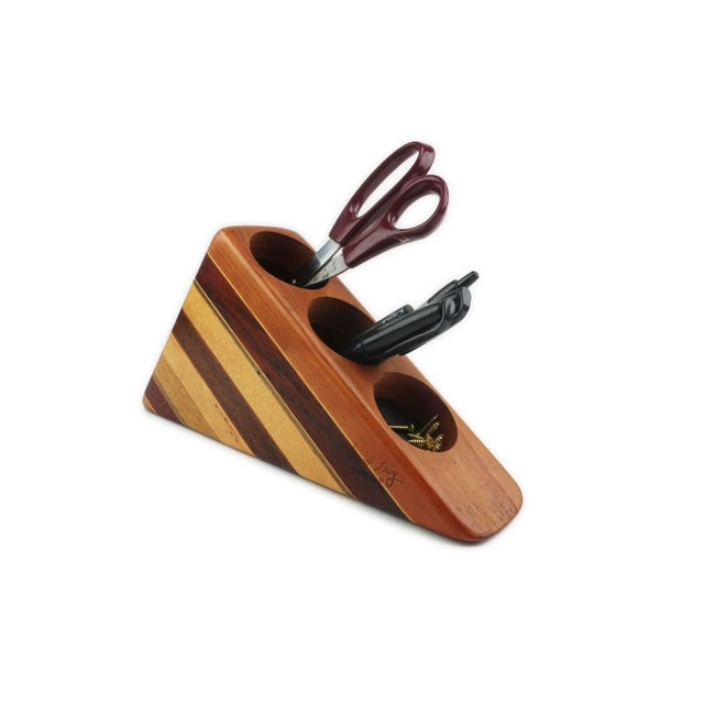 A signed vintage desk organizer made from pieces of assorted hardwoods in a triangle design. Has two slots for pens,...