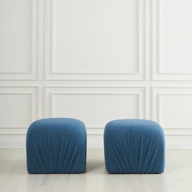 A versatile pair of vintage poufs from the 1980s, reupholstered in a textured blue wool with ruching along the sides....