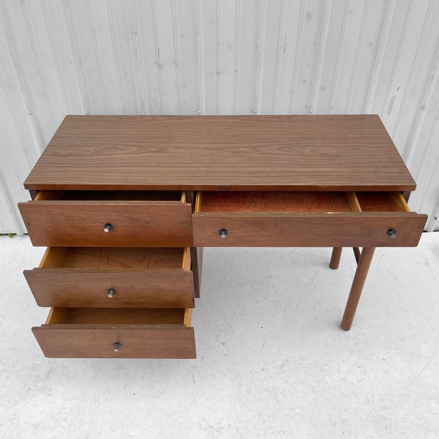 This mid-century modern writing desk offers spacious drawers in a compact package. The vintage walnut finish, tapered...