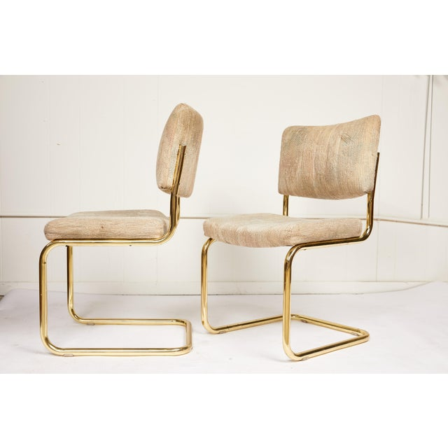 20th century pair of cantilever chairs made of tubular brass frames and manufactured by Chromcraft. The chair seats and...