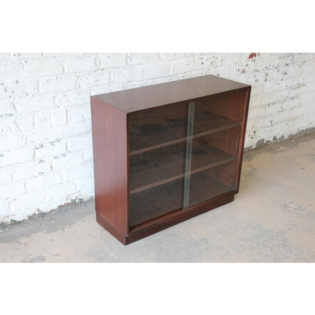 Offering a very nice mid-century modern glass front bookcase designed by T.H. Robsjohn-Gibbings for Widdicomb. The...