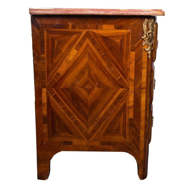 Period French kingwood and tulipwood inlaid Regence commode with gilt metal mounts and shaped marble top, circa 1720.