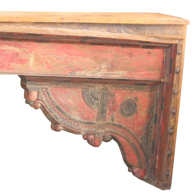 Made from a 19th Century teak carved beam, this impressive console features floral carved details and its original red...