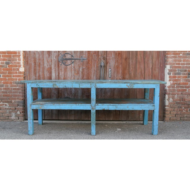 A charming antique farmhouse table, it features a solid top that retains its original painted finish, stands on six chunky...