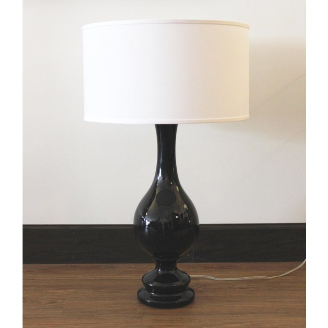 A classic and versatile table lamp in glossy black ceramic with a white cloth shade. Larger in size--would look terrific...
