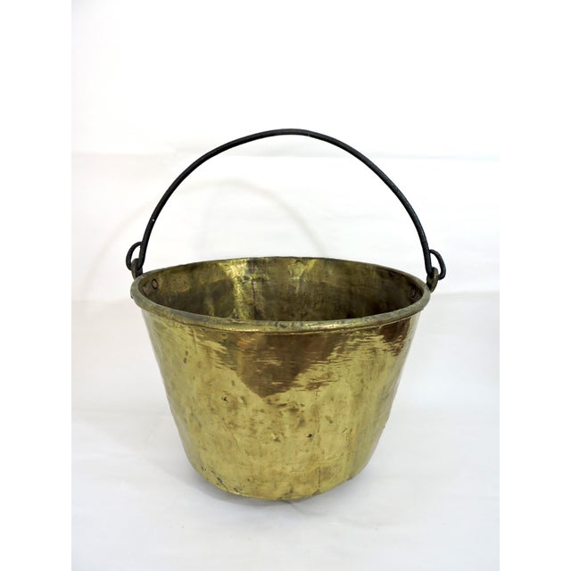 Antique solid brass fire wood or kindling bucket with heavy cast iron handle dating from the mid-late 1800's. The hammered...