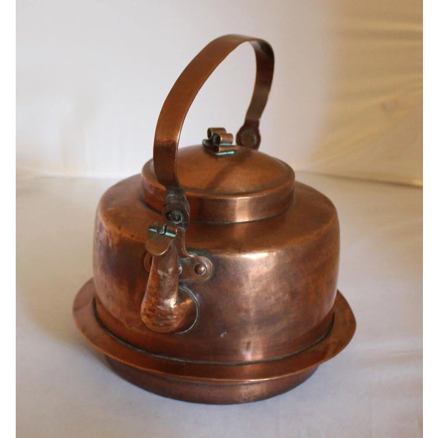 Mid-19th century large tea kettle with spout flap and flare to sit in tripod on fire. Curled knop and dovetailed...
