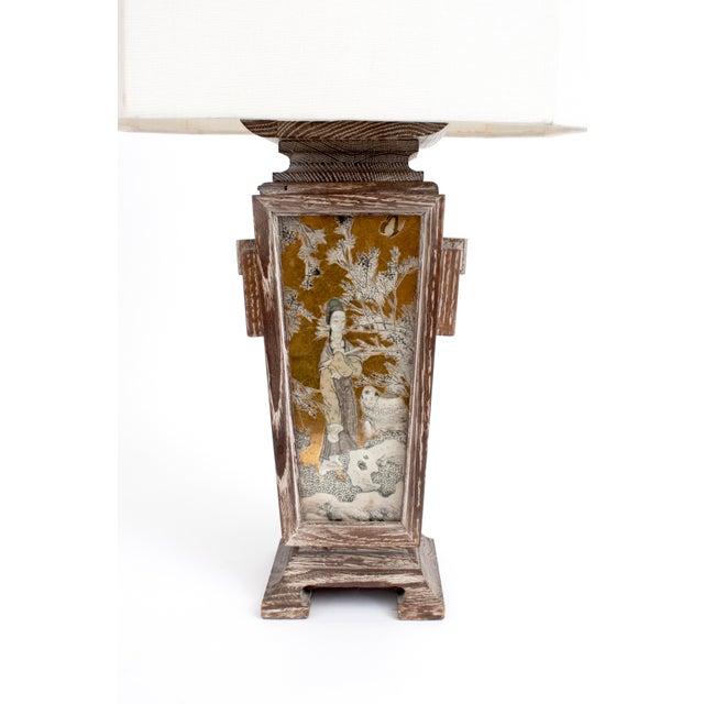 Stunning lamp by James Mont with coursed oak, reverse-painted gilded glass and brass details. Linen octagonal shade. Some...