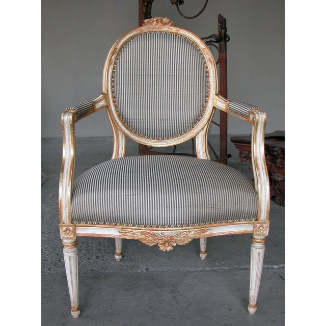 An elegant pair of Swedish Gustavian style ivory painted and parcel-gilt oval-back armchairs; each arching crest...