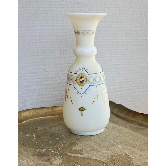 A delightful French hand painted opaline vase with very delicate paintings in the design of garlands in gold, blue and...