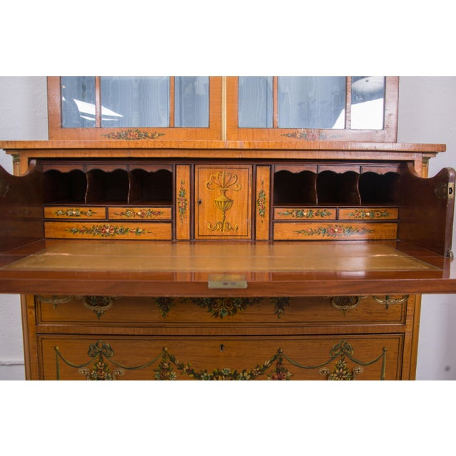 A fine example of an English Adams style painted satinwood secretary painted overall with delicate flowers and swags. The...