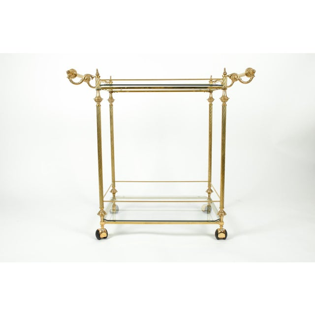 Vintage French solid brass wheeled bar cart / tea trolley with glass shelves and two side handles. The Bar cart / tea...