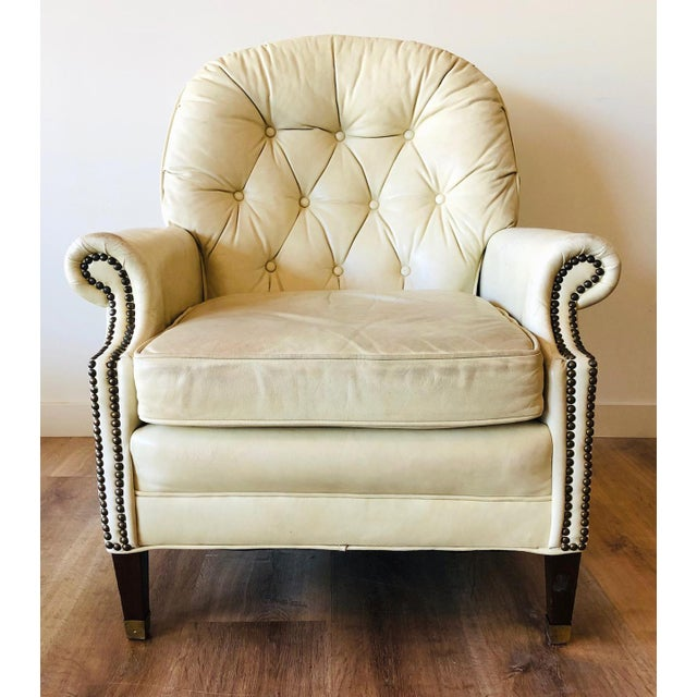 Off-white leather tufted chair with broken in leather and wear on the arm rests. Brass rivet detailing. Walnut legs with...