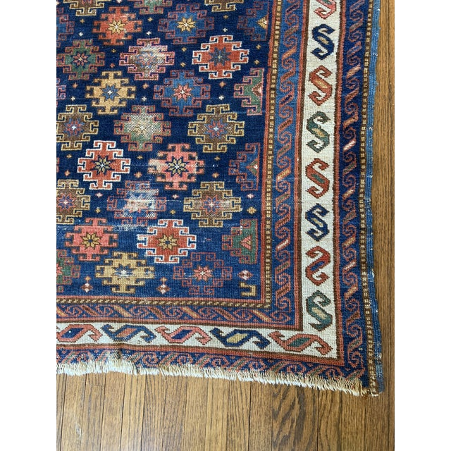 Beautiful hand knotted rug with geometric motif. Features various colors with fringe on ends. Rug has overall wear.