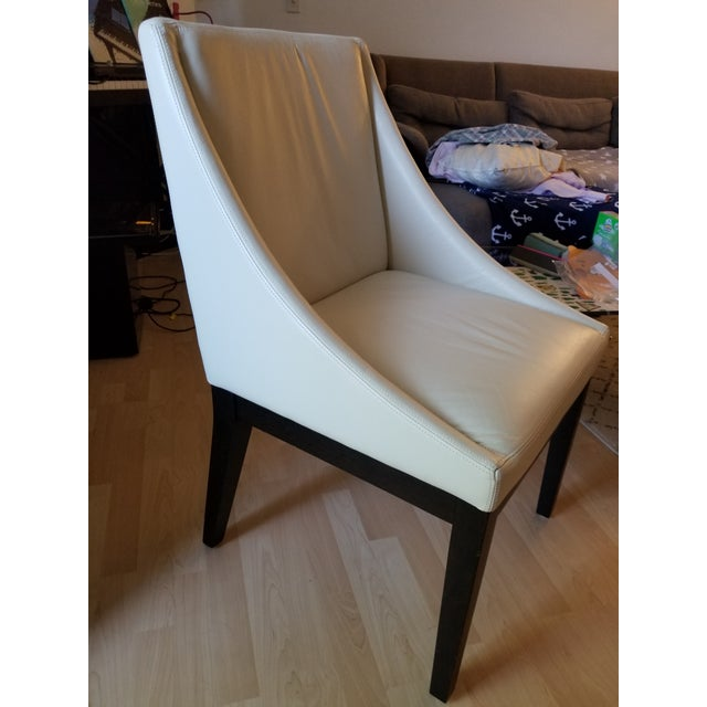 West Elm white curved leather dining chair, perfect touch of elegance to use as an office chair as well. Solid wooden legs...