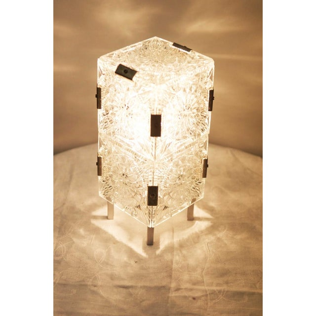 This mid century table lamp was designed in the 1960s. It consists of an aluminum frame with an E27 socket and nine...