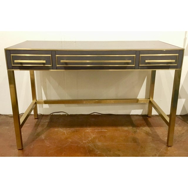 Stylish modern Currey & Co. Arden Desk/Vanity, brass, glass, three gray suede lined drawers. Showroom floor sample,...