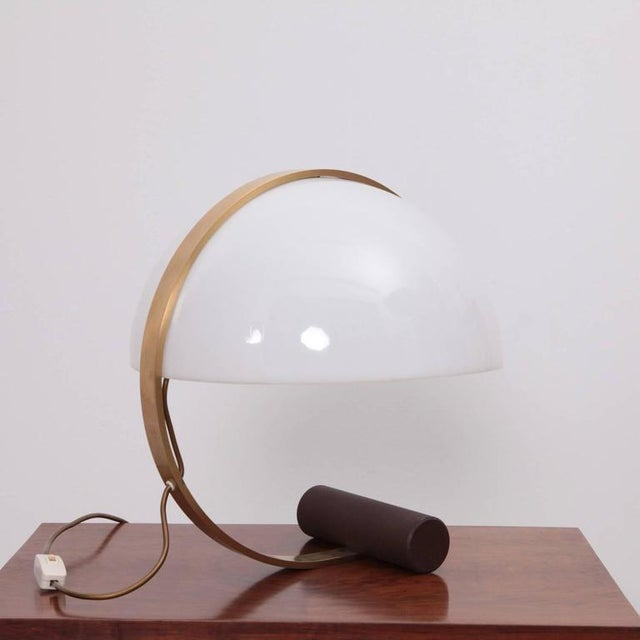 Beautiful curved lamp by Harvey Guzzini from the 1970s. Rare version in brass, wood with white plexiglass shade. 1x E27....