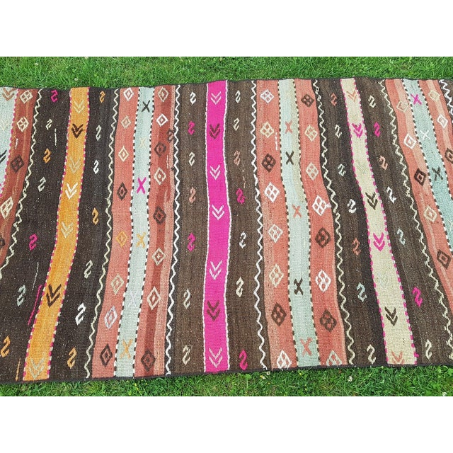 This is a vintage handmade wool kilim rug from the Konya region of Turkey. The piece was made in the 1980s.