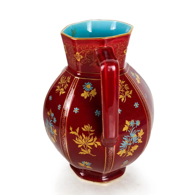 Red octagonal floral pitcher with light blue ceramic interior and gilded palm trees.