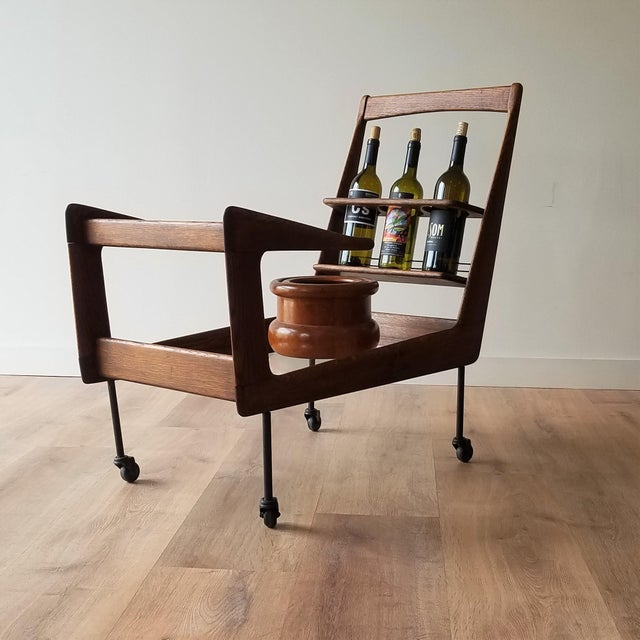 An angular Mid-Century Modern bar cart made in Italy. This bar cart has two glass shelves and three bottle holders. In...